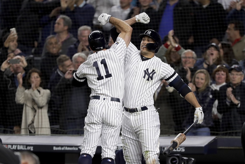 New York Yankees' Brett Gardner (11) celebrates with Giancarlo Stanton after hitting a solo home run against the Minnesota Twins during the sixth inni...