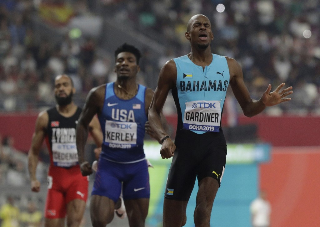 Steven Gardiner of Bahamas, right, wins the gold medal in the the men's 400 meter final at the World Athletics Championships in Doha, Qatar, Friday, O