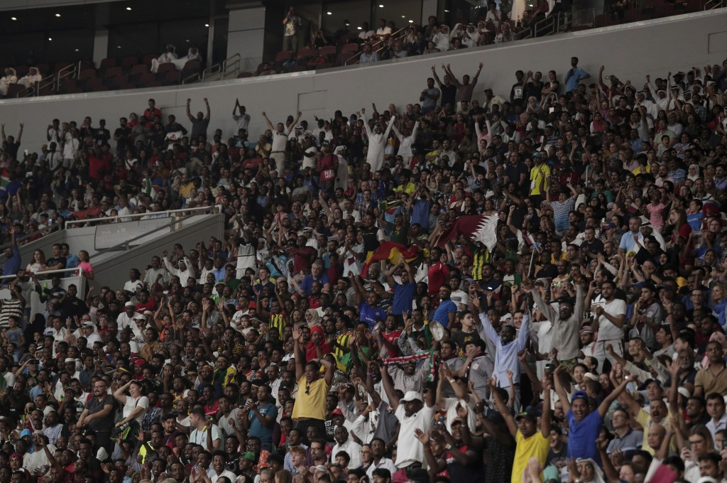 Spectators celebrate as Mutaz Essa Barshim, of Qatar, makes a clearance in the men's high jump final at the World Athletics Championships in Doha, Qat...
