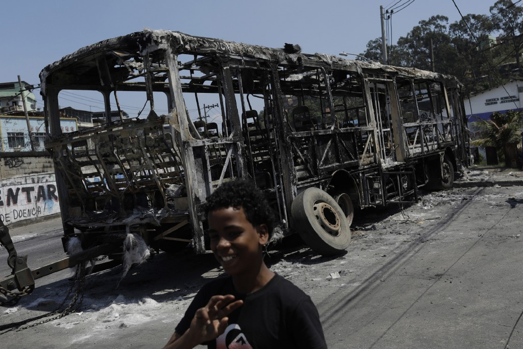 A boy walks past the skeleton of a bus that was set on fire during overnight violent confrontations at the Costa Barros neighborhood of Rio de Janeiro