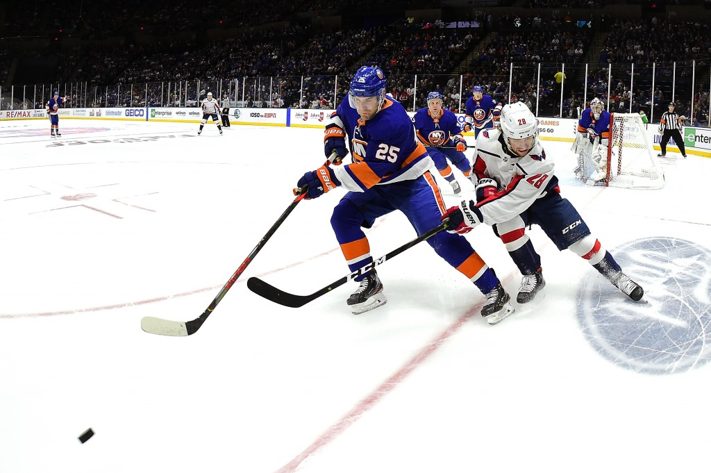 New York Islanders defenseman Devon Toews (25) is defended by Washington Capitals left wing Brendan Leipsic (28) during the first period of an NHL hoc