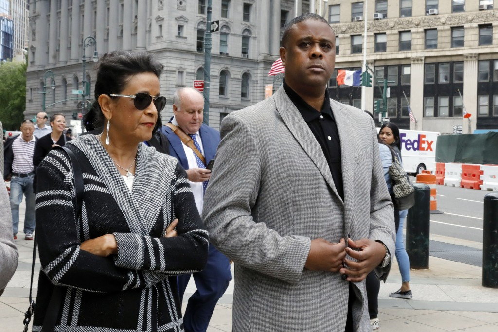 Former amateur basketball league director Merl Code, right, leaves federal court after sentencing, Friday, Oct. 4, 2019, in New York. Code was sentenc