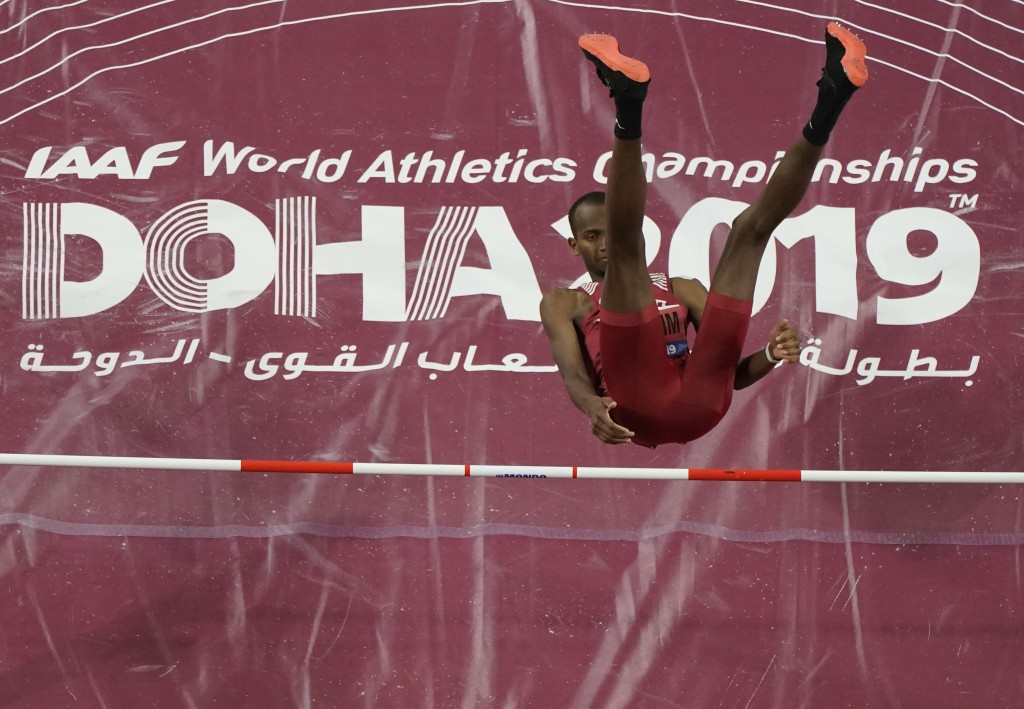 Mutaz Essa Barshim, of Qatar, clears the bar during the men's high jump finals at the World Athletics Championships in Doha, Qatar, Friday, Oct. 4, 20