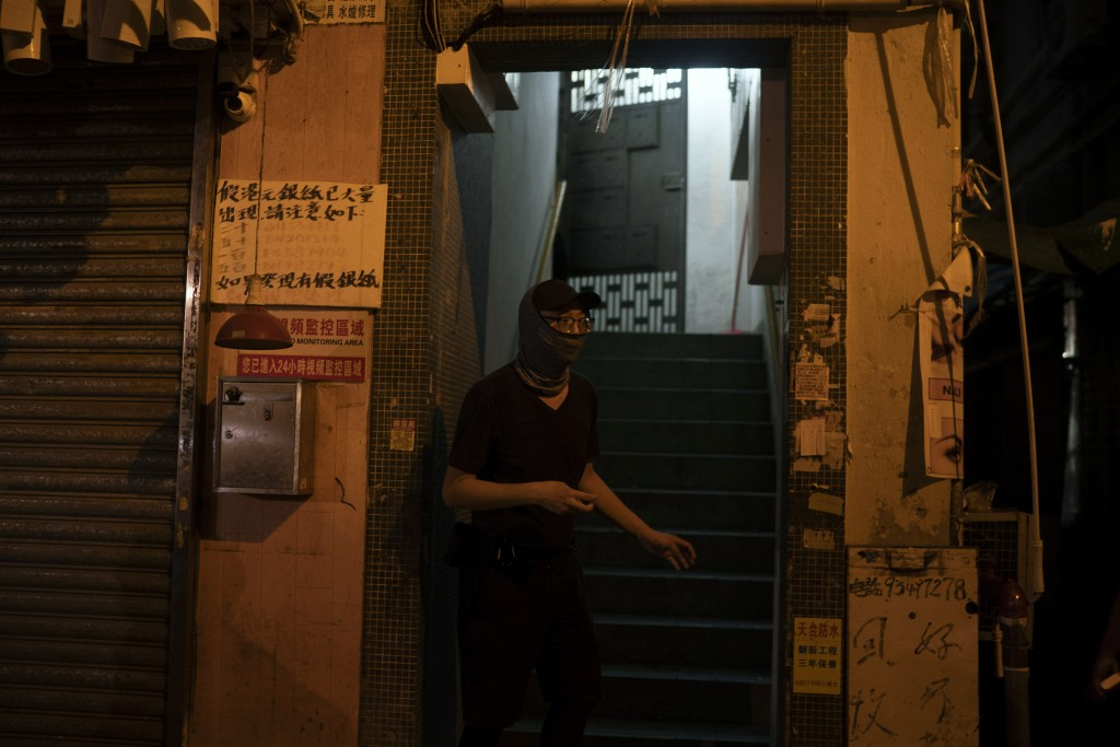 A protester seeks shelter in a building after police fired tear gas in Hong Kong on Friday, Oct. 4, 2019. Masked protesters streamed into Hong Kong st