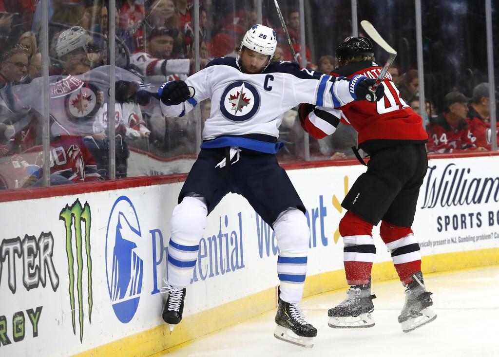 New Jersey Devils defenseman Sami Vatanen (45) checks Winnipeg Jets right wing Blake Wheeler (26) during the first period of an NHL hockey game Friday