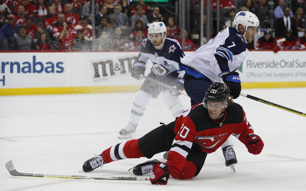 New Jersey Devils center Blake Coleman (20) falls to the ice after scoring a goal next to Winnipeg Jets defenseman Dmitry Kulikov (7) during the secon...
