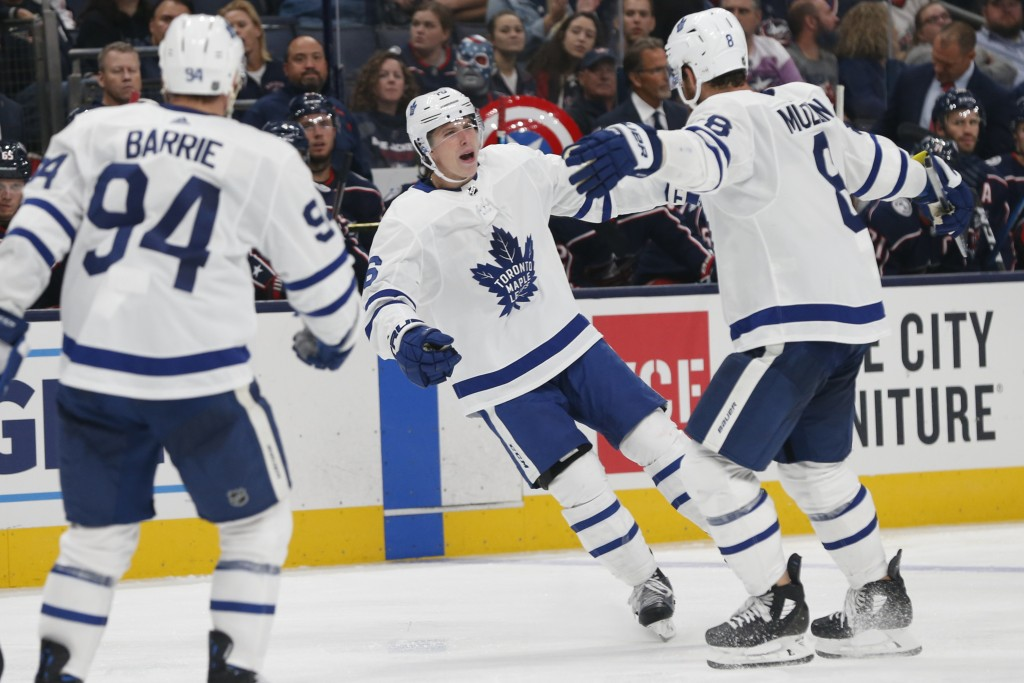 Toronto Maple Leafs' Mitchell Marner, center, celebrates a goal against the Columbus Blue Jackets during the third period of an NHL hockey game Friday...