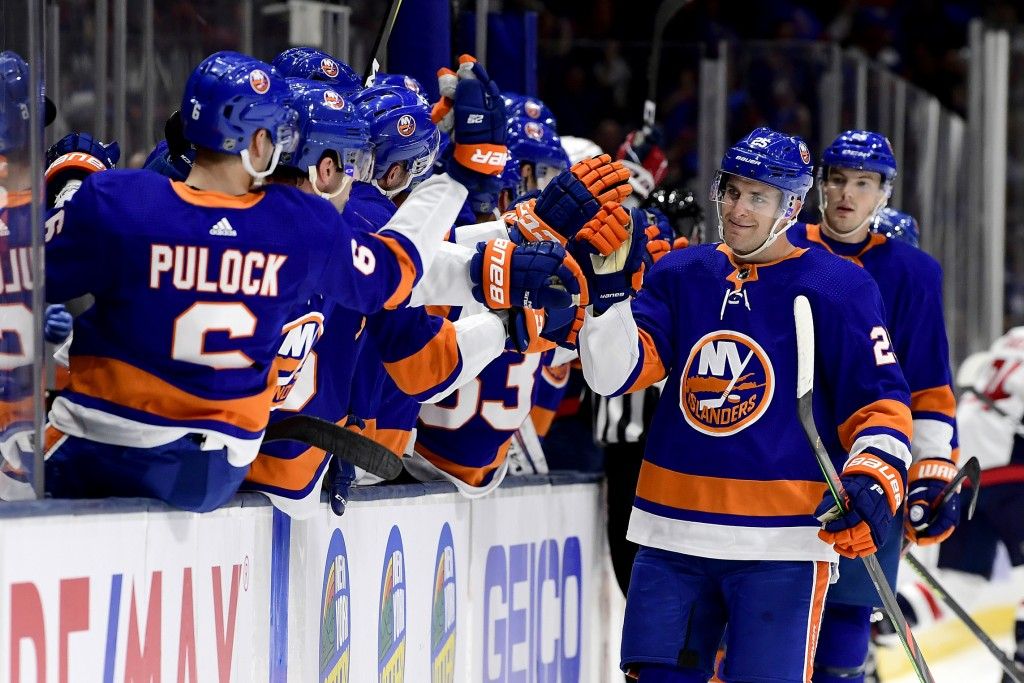 New York Islanders defenseman Devon Toews (25) is congratulated by his teammates after scoring a goal, against the Washington Capitals during the firs