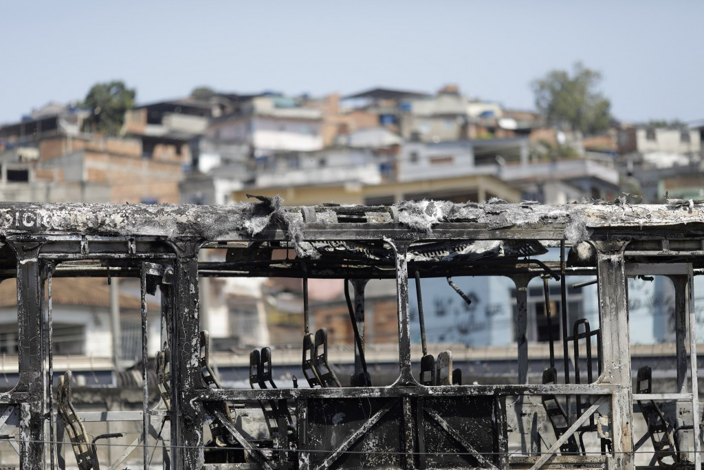 The skeleton of a bus that was set on fire during overnight violent confrontations stands at the Costa Barros neighborhood of Rio de Janeiro, Brazil, ...