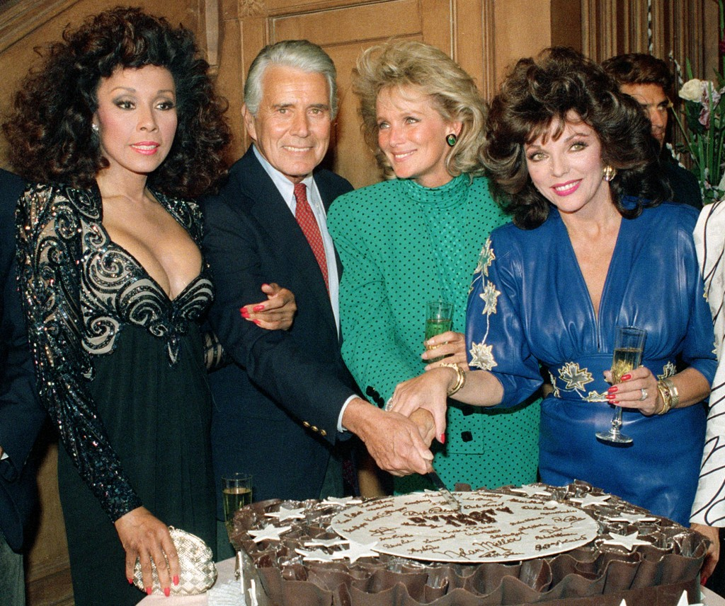 """FILE - This Sept. 24, 1986 file photo shows, Diahann Carroll, John Forsythe, Linda Evans and Joan Collins from """"Dynasty"""" cutting a cake to commemorate"""