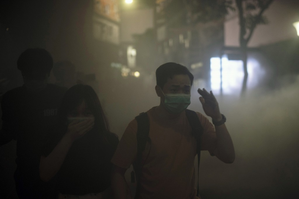 A man and woman walks through smoke from a fire near a subway station entrance in Hong Kong on Friday, Oct. 4, 2019. Masked protesters streamed into H