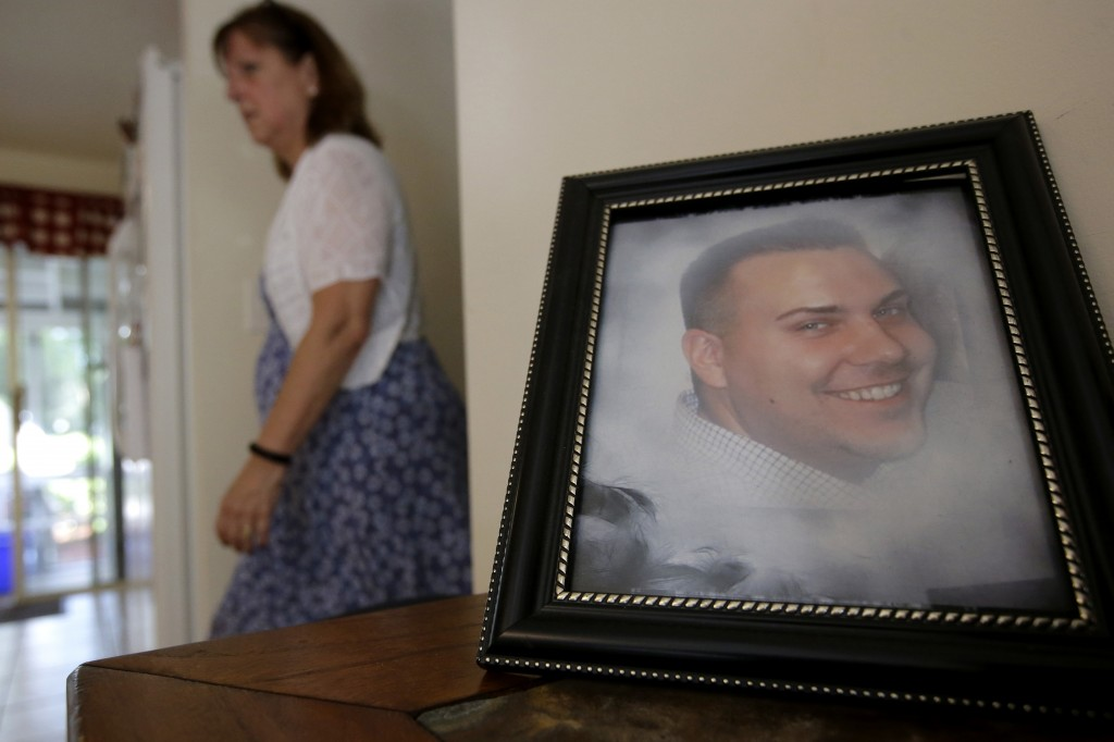 FILE - In this Tuesday, June 19, 2018 file photo Cheryl Juaire walks past a photo of her son, Corey Merrill, at her home in Marlborough, Mass. Victims