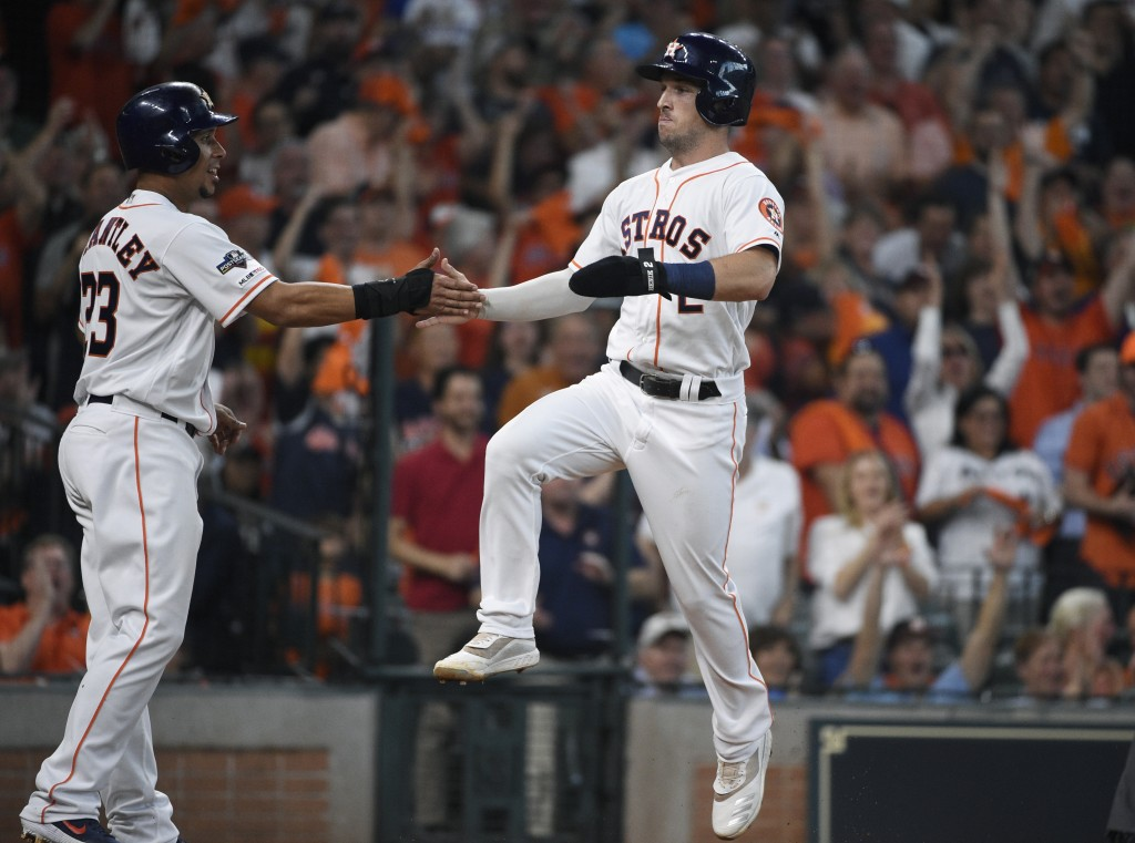 Houston Astros' Alex Bregman (2) celebrates with teammate Michael Brantley (23) as he scores against the Tampa Bay Rays in the fifth inning during Gam...