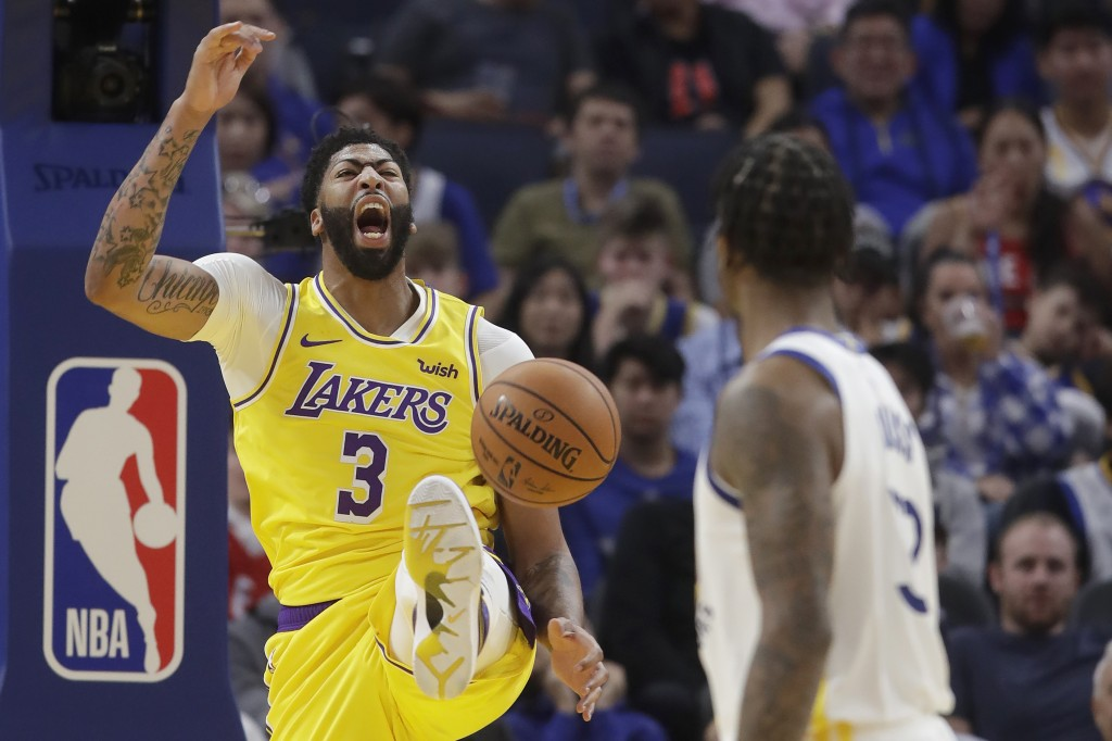 Los Angeles Lakers forward Anthony Davis (3) yells after dunking against the Golden State Warriors during the first half of a preseason NBA basketball...