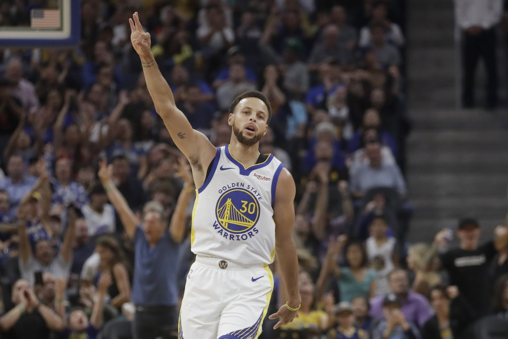 Golden State Warriors guard Stephen Curry gestures after making a 3-point basket against the Los Angeles Lakers during the first half of a preseason N...