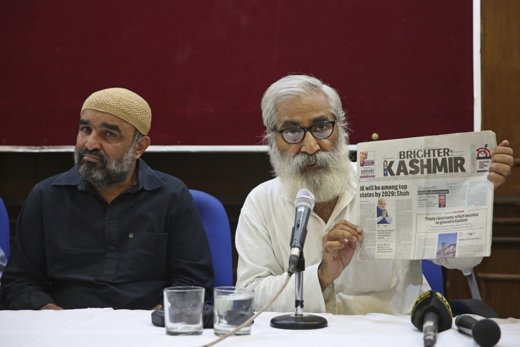 Indian activist and education reformer Sandeep Pandey, right, holds a local daily newspaper of Srinagar, as he addresses a press conference in New Del...