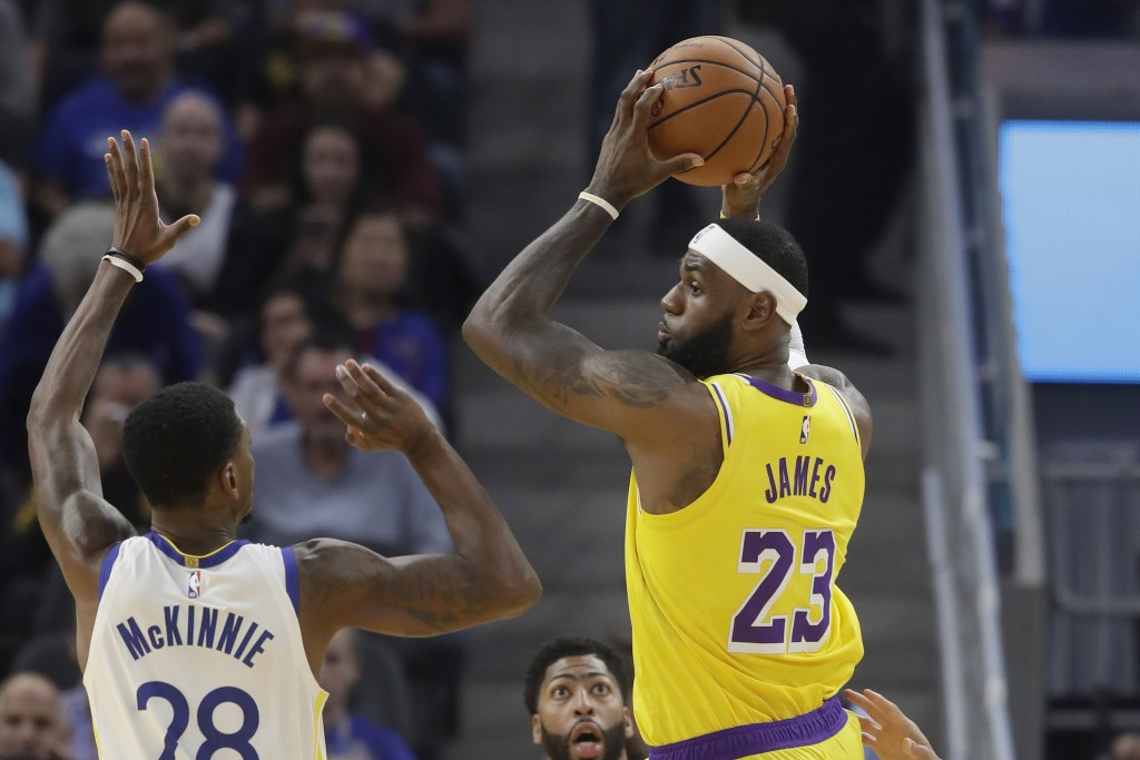 Los Angeles Lakers forward LeBron James (23) passes the ball against Golden State Warriors forward Alfonzo McKinnie (28) during the first half of a pr...