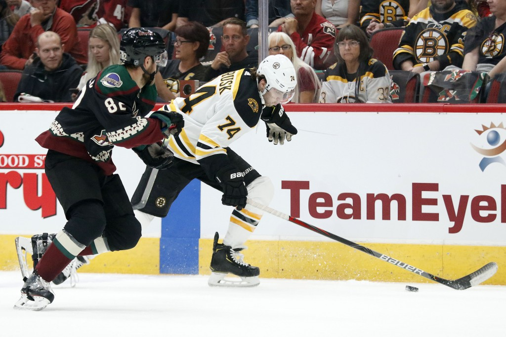Boston Bruins' Jake BeBrusk (74) runs down the puck against the Arizona Coyotes' Jordan Oesterle (82) during the first period of an NHL hockey game Sa...