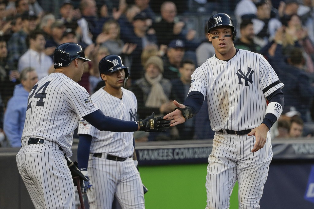 New York Yankees' Aaron Judge, right, celebrates with teammates after scoring against the Minnesota Twins during the third inning of Game 2 of an Amer...