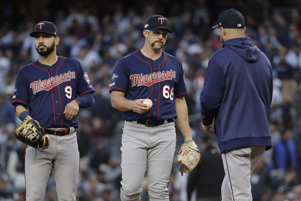 Minnesota Twins starting pitcher Randy Dobnak (68) hands the ball to manager Rocco Baldelli as he leaves the game during the third inning of Game 2 of...
