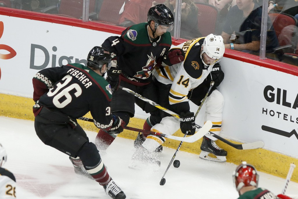 Boston Bruins' Chris Wagner (14) gets pinned up against the boards by the Arizona Coyotes' Niklas Hjalmarsson (4) and Christian Fischer (36) during th...