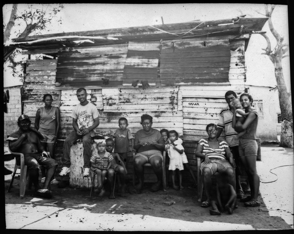 The Elizalzabal and Silva families, who fish for a living, pose for a group portrait outside one of their family's homes, on the shore of oil-contamin