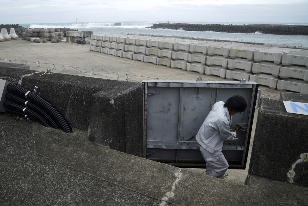 A Kiho town official closes a door of a coastal levee as Typhoon Hagibis approaches at a port in town of Kiho, Mie Prefecture, Japan Friday, Oct. 11, ...