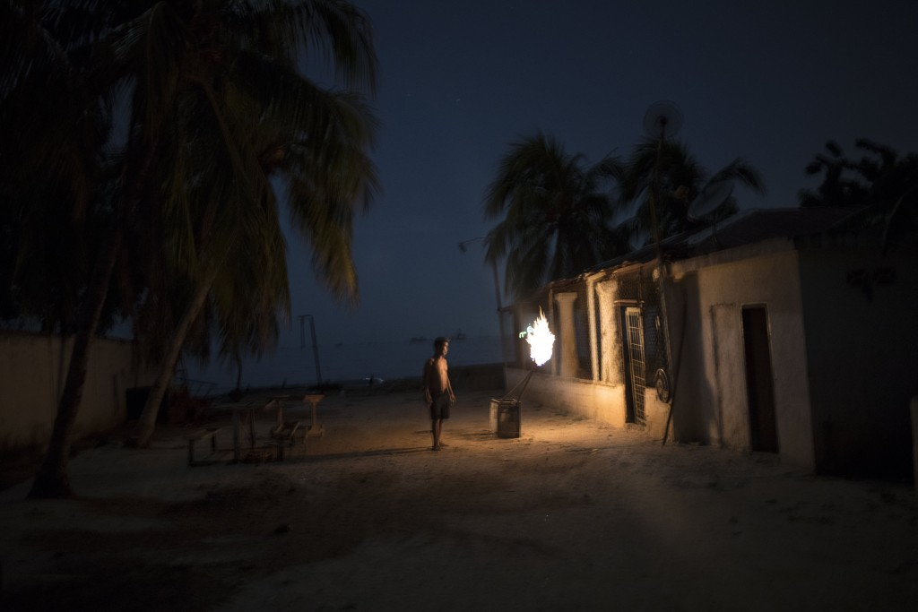 """During a blackout, a man is illuminated by torches made out of crude oil, and known as """"mechurrios,"""" the name for the flares that burn excess gas on t..."""