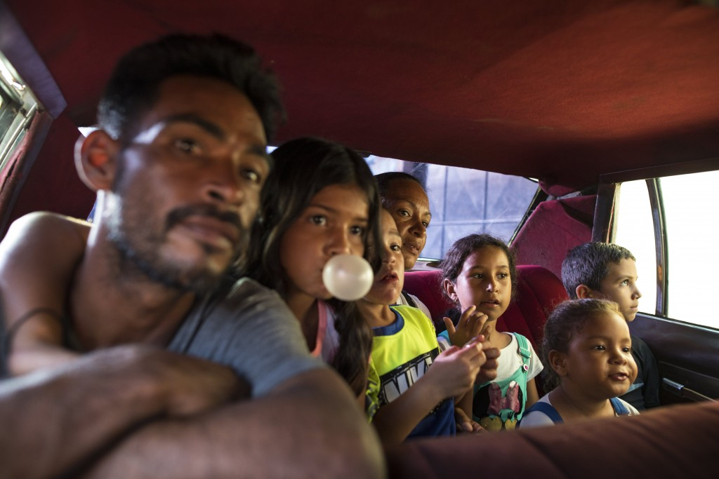 Fisherman Yanis Rodríguez and his family ride in the back of a 1970's taxi, driven by a PDVSA state oil worker who makes extra money as a taxi driver,...
