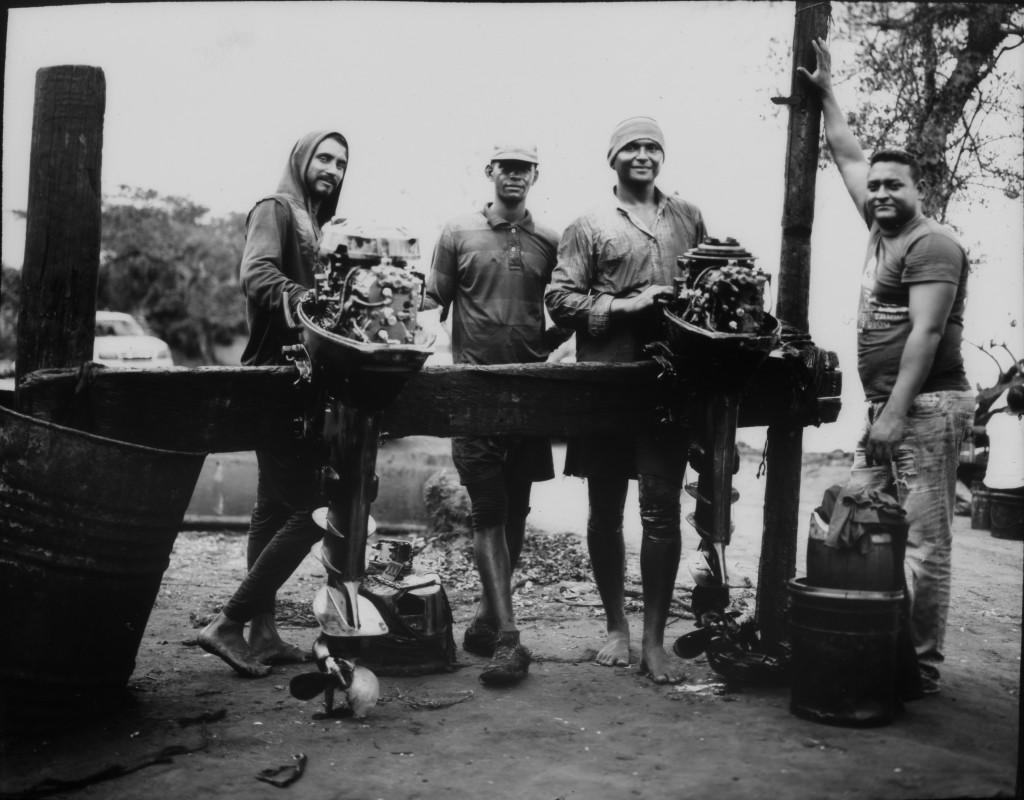 Giovani Blanco, the owner of several fishing boats, right, and his assistants stop to pose for a portrait as they repair boat motors that were damaged