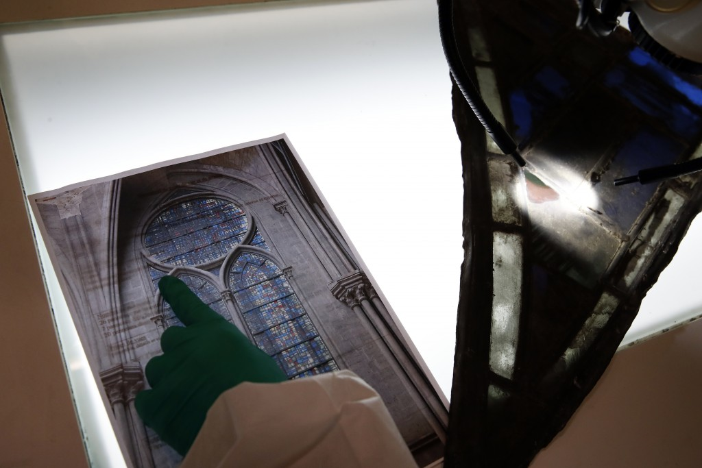 In this photo taken on Wednesday, Oct. 9, 2019, Glass specialist Claudine Loisel checks the Notre Dame cathedral's stained-glass windows in a lab at C