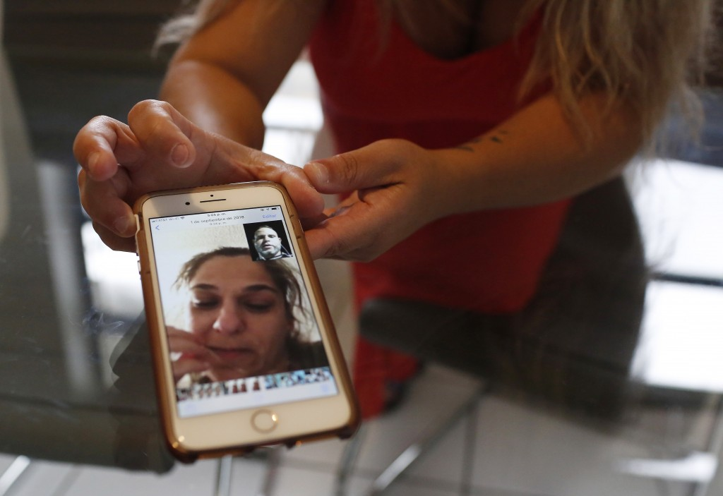 In this Aug. 6, 2019, photo, Barbara Rodriguez shows a photograph on her phone of her talking to her husband, Pablo Sanchez at her home in Hialeah, Fl...