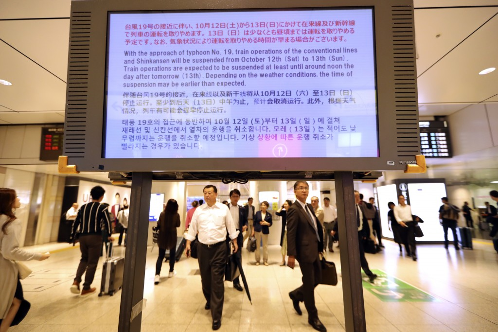 An electric board shows a notice on suspending operations of the Shinkansen or bullet train on Oct. 12-13 due to Typhoon Hagibis, at Tokyo Station in ...