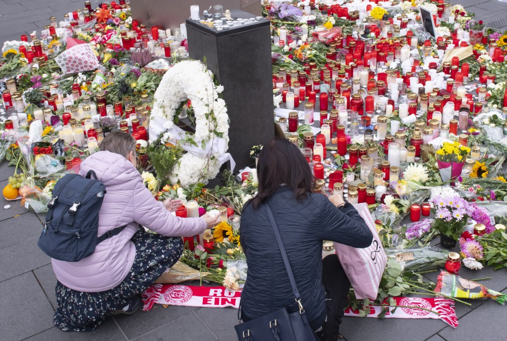 People place down flowers and candles at the marketplace in the old town of Halle, Germany, Friday, Oct. 11, 2019. A heavily armed assailant ranting a...