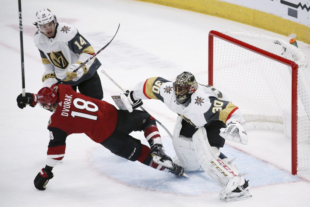 Arizona Coyotes left wing Christian Dvorak (18) gets clobbered by Vegas Golden Knights goaltender Malcolm Subban (30) and defenseman Nicolas Hague (14...