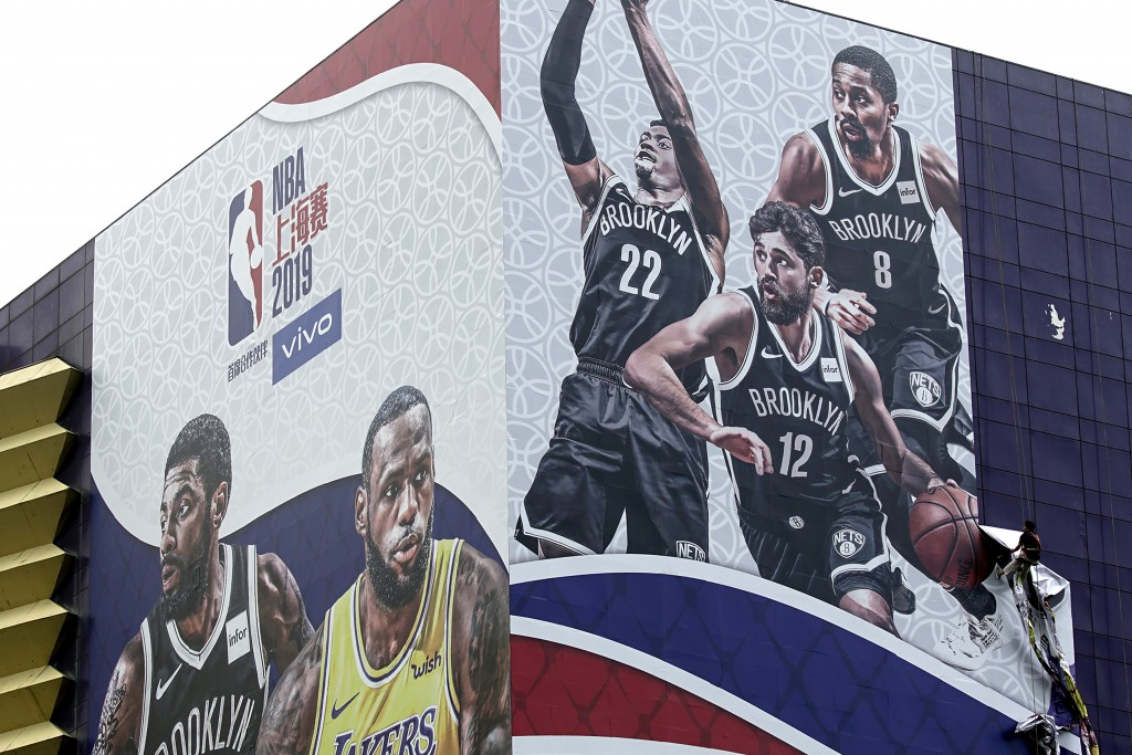 In this Oct. 9, 2019, photo, a worker takes down a billboard advertising an NBA preseason basketball game on Thursday between the Los Angeles Lakers a...