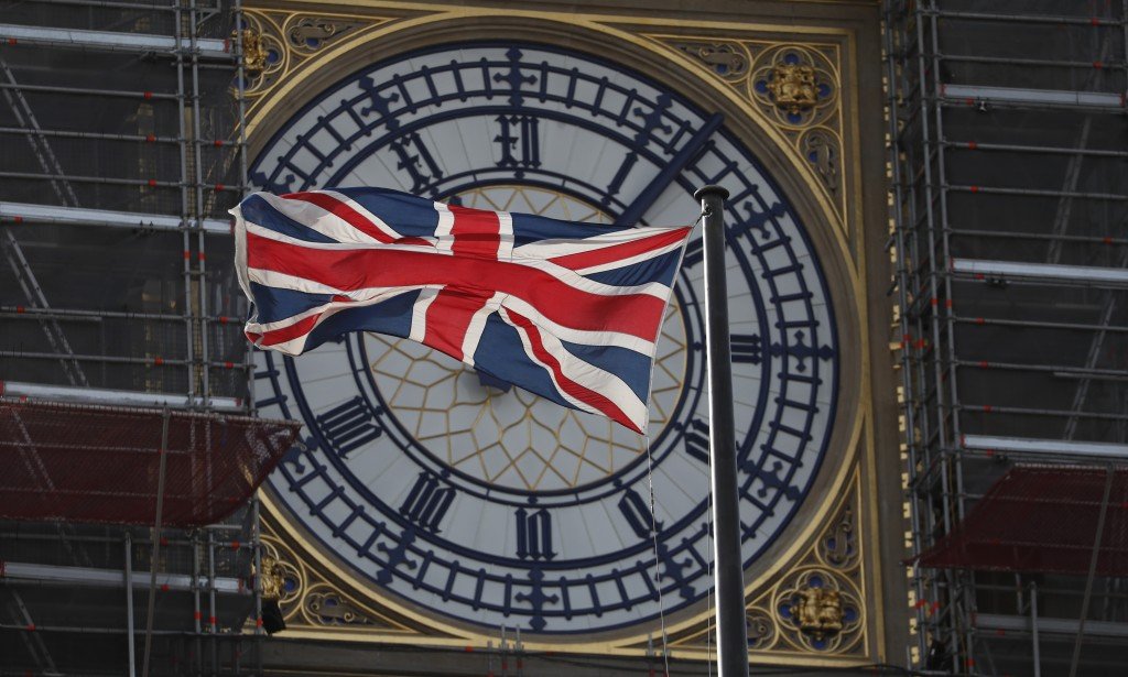 The Union flag of Great Britain and Northern Ireland flies in front of the clock face of the Queen Elizabeth Tower, that holds the bell known as 'Big