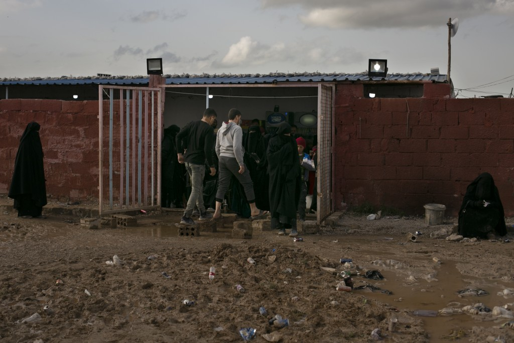 In this March 31, 2019, photo, women stand outside a small shop al-Hol camp, in Hasakeh province, Syria, Sunday, March 31, 2019.  As Turkish troops in...