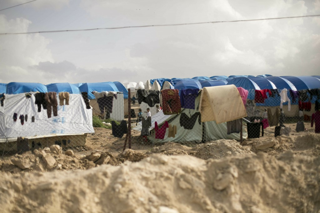 FILE - In this Sunday, March 31, 2019 file photo, laundry dries on a chain link fence in an area for foreign families, at al-Hol camp in Hasakeh provi...