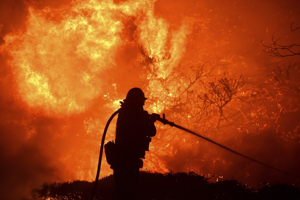The Saddleridge fire flares up near a firefighter in Sylmar, Calif., Thursday, Oct. 10, 2019. (AP Photo/Michael Owen Baker)