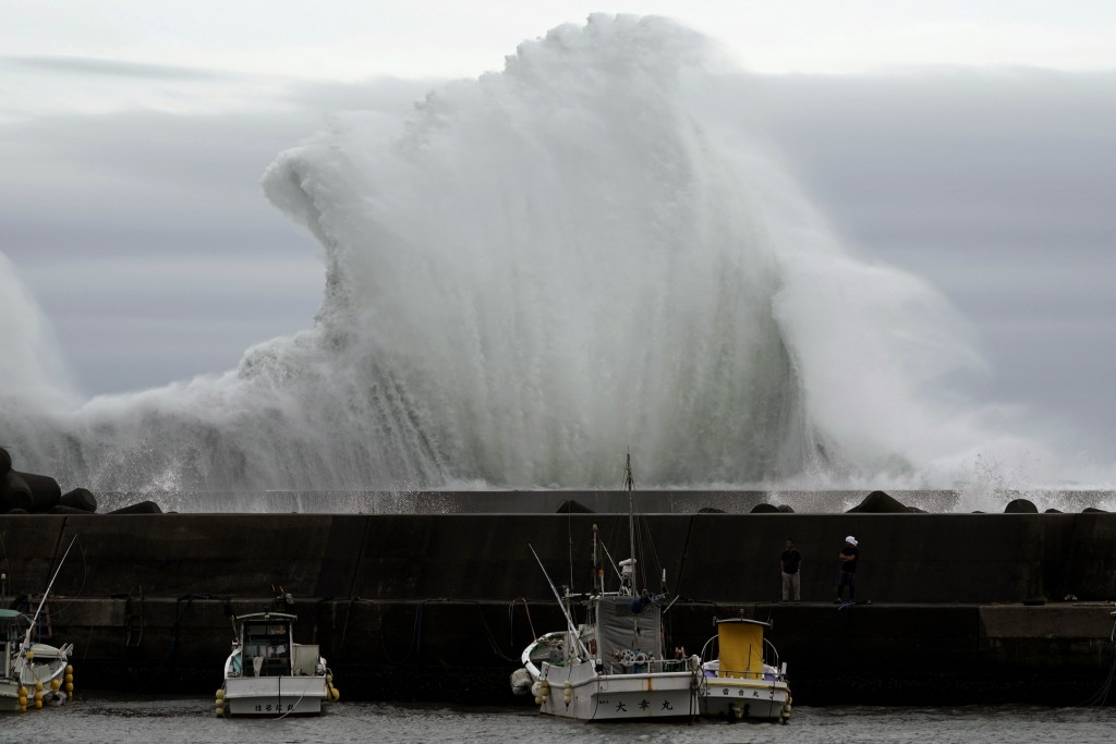 Men look at fishing boats as surging waves hit against the breakwater while Typhoon Hagibis approaches at a port in town of Kiho, Mie Prefecture, Japa...