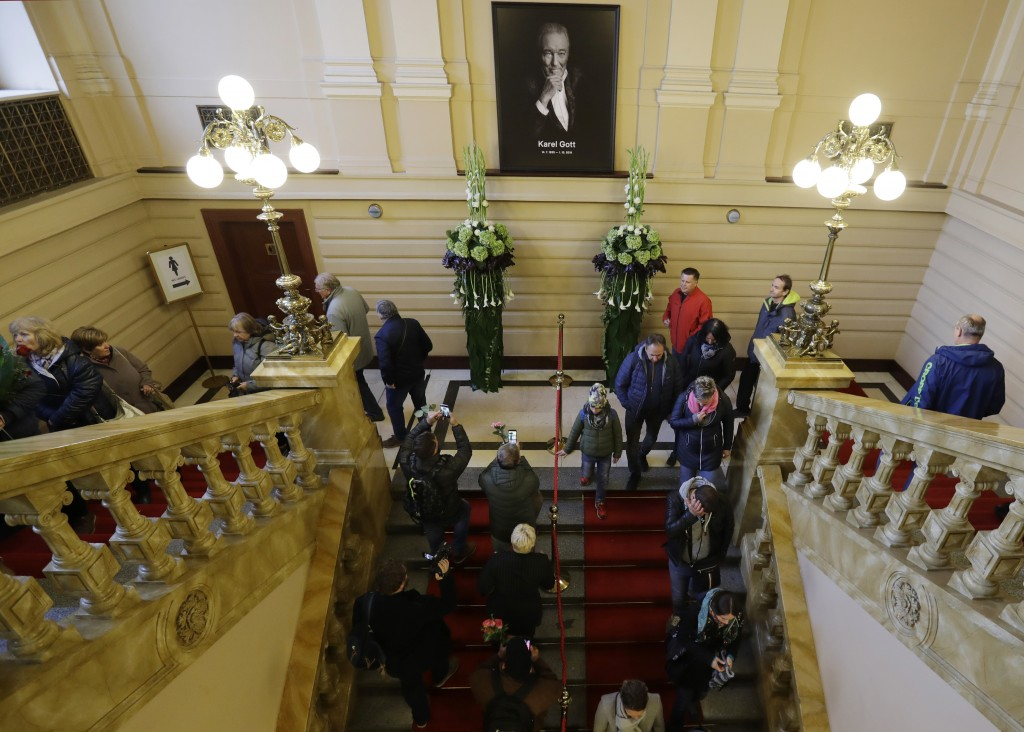 People arrive to pay respect to late Czech famous pop singer Karel Gott during a memorial service in Prague, Czech Republic, Friday, Oct. 11, 2019. Go