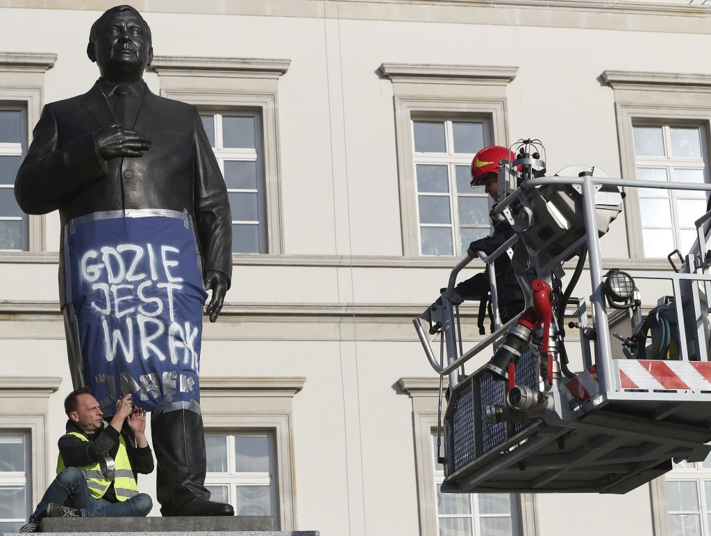 A man sits on a monument to Poland's late president Lech Kaczynski in downtown Warsaw, Poland, Friday, Oct. 11, 2019. He wrapped it in a banner readin