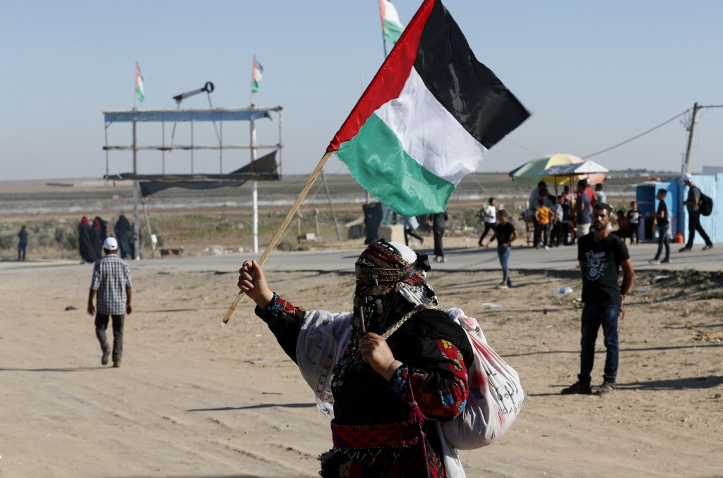 In this Sept. 25, 2019 photo, a Palestinian woman waves a national flag during a alternative protest organized by activist Ahmed Abu Artima near the s