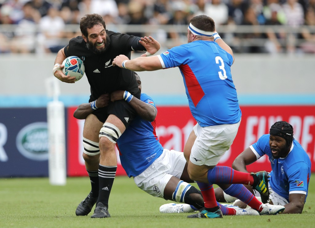 New Zealand's Samuel Whitelock looks to fend off Namibia's AJ De Klerk, right, during the Rugby World Cup Pool B game at Tokyo Stadium between New Zea...