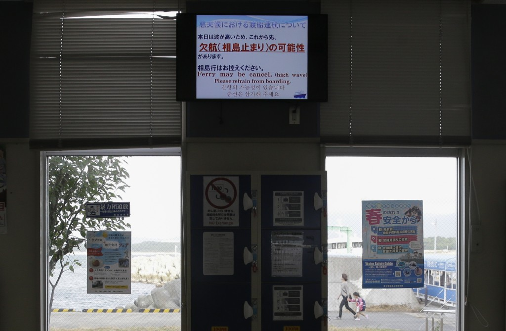 A ferry station shows a sign that cancels boat trips at the Shigu port in Fukuoka, southern Japan on Friday, Oct. 11, 2019. A powerful typhoon was for