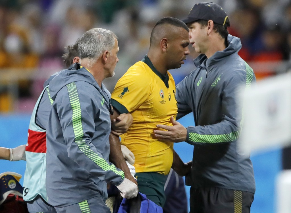 Australia's Kurtley Beale is assisted from the field after suffering a head injury during the Rugby World Cup Pool D game at Shizuoka Stadium Ecopa be