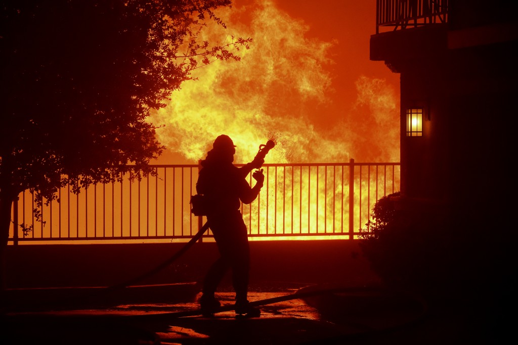 In this Thursday, Oct. 10, 2019 photo, a firefighter waits for water as the Saddleridge fire flares up near homes in Sylmar, Calif. (AP Photo/Michael