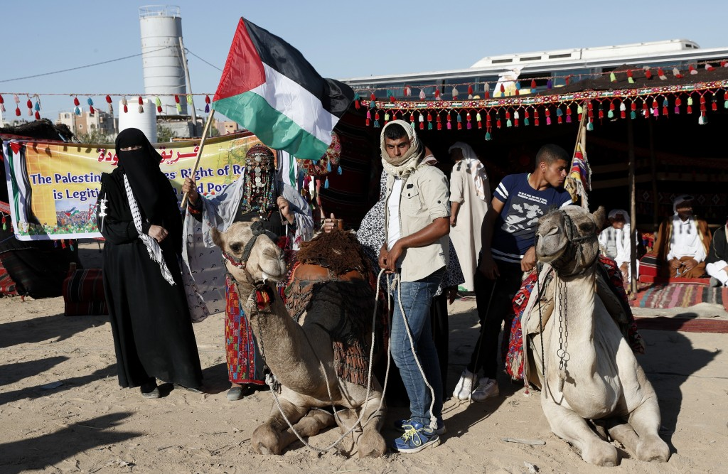 In this Sept. 25, 2019 photo, Palestinians attend an alternative protest organized by activist Ahmed Abu Artima near the separation fence between the