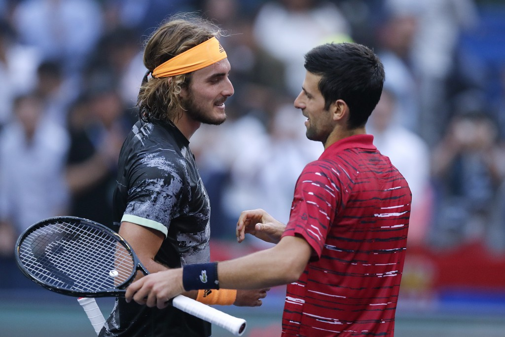 Stefanos Tsitsipas, left, of Greece is congratulated by Novak Djokovic of Serbia after winning in their men's singles quarterfinals match at the Shang...